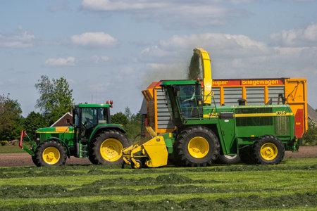 ACHTERHOEK, THE NETHERLANDS - MAY 2, 2011: John Deere 6910S tractor and John Deere 6750 Forage Harvester at work.