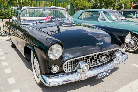 restored: DEN BOSCH, THE NETHERLANDS - MAY 10, 2015: Black 1956 Ford Thunderbird classic cabriolet car.
