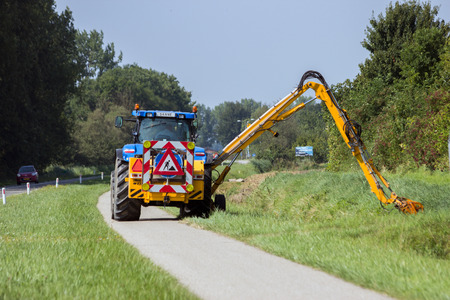 ACHTERHOEK, NETHERLANDS - AUG 23, 2013: Tractor mowing roadside grass shoulder.