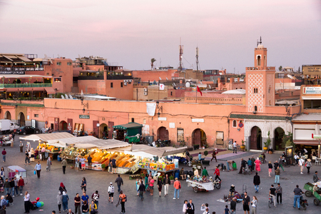 MARRAKESH, MOROCCO - APR 29, 2016: Mosque and restaurants with tourists near the souks on the Djemaa-el-Fna square in Marrakesh.