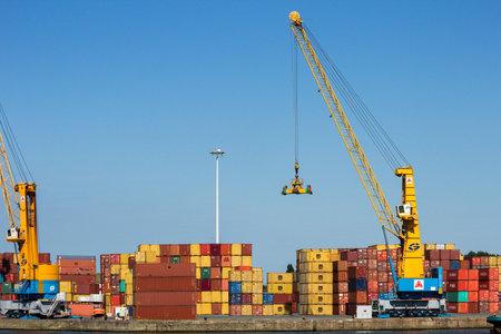 ANTWERP, BELGIUM - JUL 9, 2013: Harbor gantry cranes and sea containers in the Port of Antwerp.