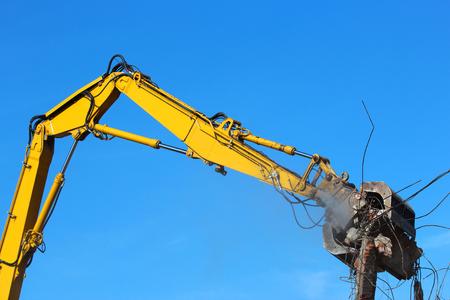 Large demolition crane dismantling a building.