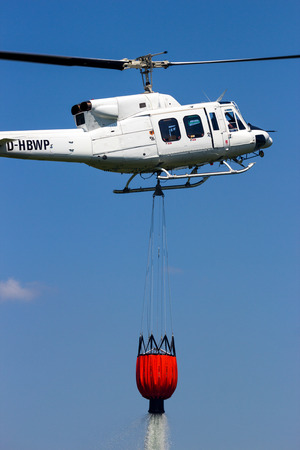 AHLEN, GERMANY - JUN 5, 2016: Bell 212 Helicopter with a water bucket used for aerial bush fire fighting.