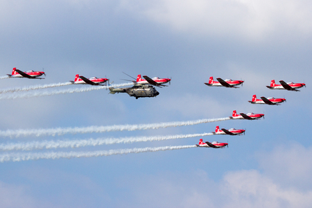 KLEINE BROGEL, BELGIUM - SEP 13, 2014: Swiss Air Force PC-7 acrobatic demonstration team in formation with a Super Puma helicopter. Editorial