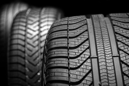 Row of car tires with a profile close-up on a black background.