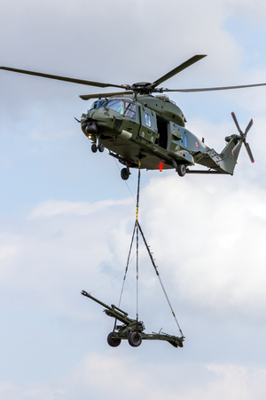 BEAUVECHAIN, BELGIUM - MAY 20, 2015: Belgian army NH90 helicopter transporting an artillery piece.