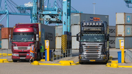 ROTTERDAM, NETHERLANDS - SEP 8, 2012: Container loaded trucks about to leave a shipping terminal in the Port of Rotterdam.