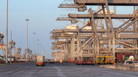 ROTTERDAM, JUL 9, 2013: Automated Guided Vehicles moving shipping containers to and from gantry cranes in a port container terminal.