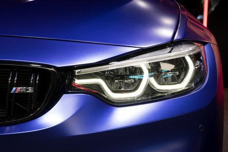 GENEVA, SWITZERLAND - MARCH 7, 2018: LED Headlight close up of a BMW M3 car presented at the 88th Geneva International Motor Show.