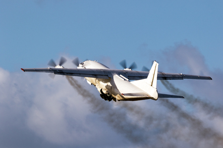 Old cargo airplane taking off with turboprop engine smoke emission. Stock Photo