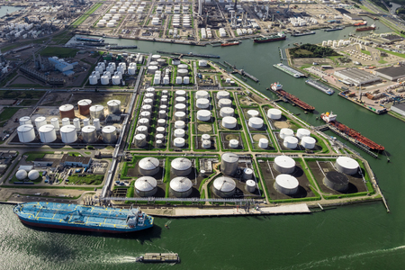 Aerial view of oil tankers and storage silo tanks at a petrochemical terminal port.