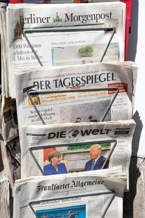 BERLIN - APR 28, 2018: Newspaper stand with various German newspapers and Angela Merkel and Donald Trump on the front cover of Die Welt newspaper. Standard-Bild - 102536169