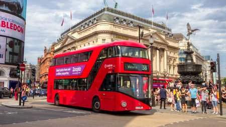 LONDON - JUL 2, 2015: Red double-decker bus driving past Picadilly Circus in London.