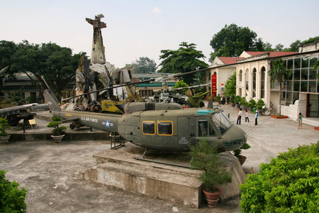 HANOI, VIETNAM - SEP 2, 2009: American UH-1 Huey helicopter stands in the Hanoi War Museum, behind it a pile of American shot down aircraft.