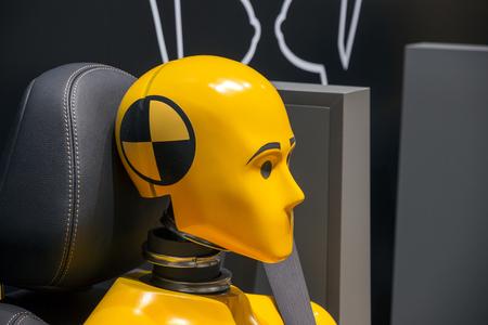 Yellow crash test dummy in a car seat. 스톡 콘텐츠
