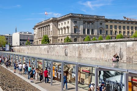 BERLIN - APRIL 28, 2018: Tourists walking past a part of the Berlin Wall at the Topography of Terror Documentation Center.
