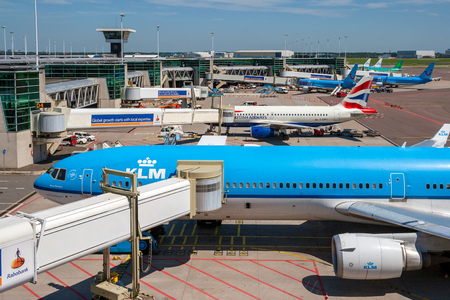 AMSTERDAM, THE NETHERLANDS - JUN 27, 2011: KLM airlines Boeing passenger plane among others at the gates of Amsterdam Schiphol Airport.