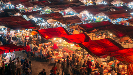 MARRAKECH, MOROCCO - APR 27, 2016: Food stalls at sunset on the Djemaa El Fna square. In the evening the large square fills with food stands, attracting crowds of locals and tourists.