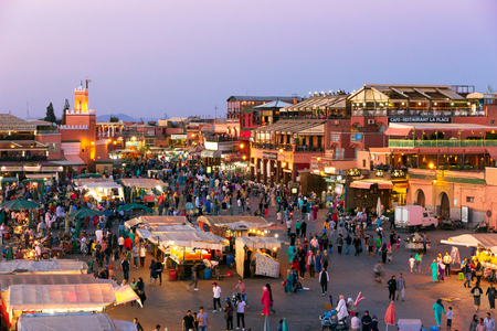 MARRAKESH, MOROCCO - APR 27, 2016: Tourists and locals on the Djemaa-el-Fna square during sunset in Marrakesh.