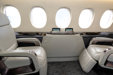 Comfortible cabin chairs in a modern business jet aircraft during flight.