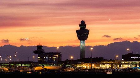AMSTERDAM, THE NETHERLANDS - JAN 9, 2019: View on Amsterdam Schiphol International Airport while planes are landing after sunset.