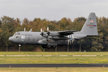 EINDHOVEN, THE NETHERLANDS - JUN 22, 2018: US Air Force Lockheed C-130H Hercules transport plane with D-Day invasion stripes landing on EIndhoven airbase.