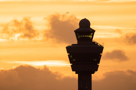 Amsterdam Schiphol International Airport control tower with a plane landing in the background during sunset. Stock Photo