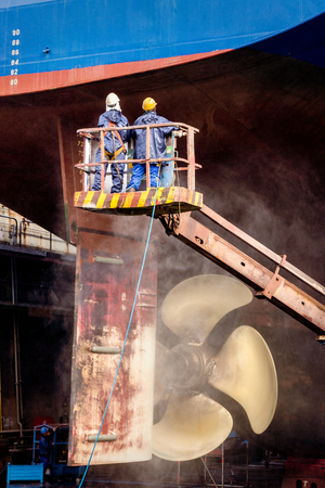 Dock workers at work on a vessel hull in a ship repair drydock. Stock Photo