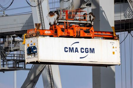 ROTTERDAM - MAR 16, 2016: Crane operator unloading a refrigerated container from a cargo ship the Port of Rotterdam.