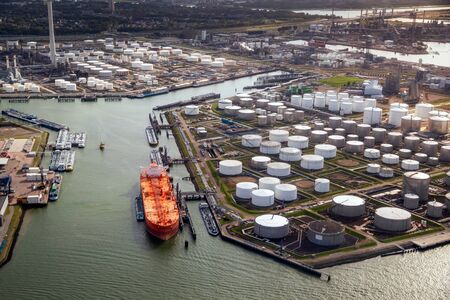 Aerial view of a large orange oil tanker moored at an oil storage silo terminal in an industrial port. Foto de archivo