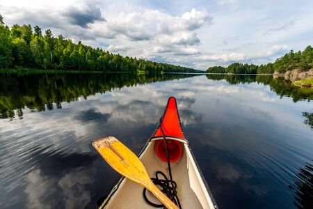 Canoeing on a calm lake in rural Sweden.
