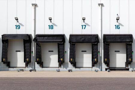 Row of loading docks with shutter doors at an industrial warehouse. Stock Photo