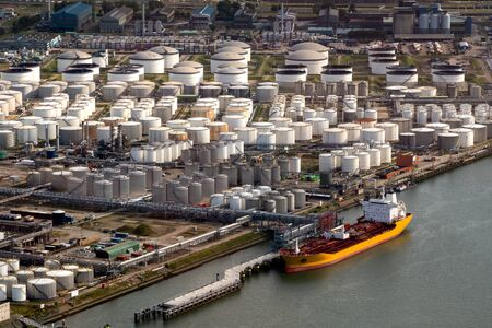 Aerial view of an oil tanker moored at an oil storage silo terminal port. 写真素材