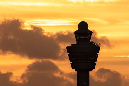 Amsterdam Schiphol International Airport control tower with a plane landing in the background during sunset.