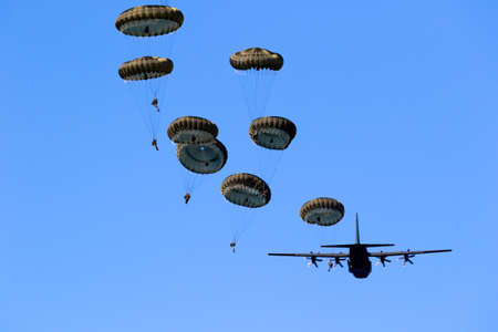 Military parachutist paratroopers jumping out of an air force airplane. Stok Fotoğraf