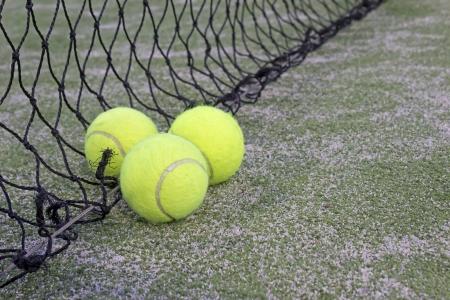 prato sintetico: Palle da tennis o paddle su erba sintetica del campo da paddle con rete sullo sfondo Archivio Fotografico