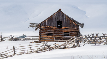 Dilapidated and weather worn 19th century homestead barn and pole fence contrasted against a snow covered background. Very strong stark contrast in this winter landscape. Avon, Montana