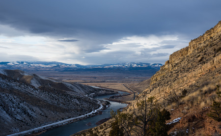 cloud capped: Wide angle late winter landscape with the Missouri River just below Toston Dam. River is flowing out the mouth of a steep rocky canyon out to flat ranching and farming valley. Snow capped mountains in the background and a big cloudy winter sky. Image take