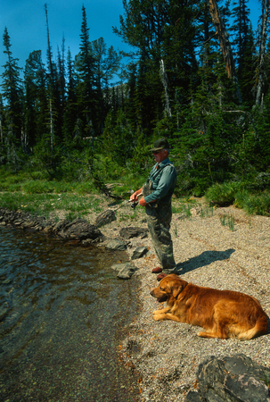 trusty: Older man fishing a beautiful high mountain lake with his trusty dog by his side. Fisherman is standing on a gravel portion of the lake shore on a gorgeous sunny summertime day with forest and blue sky in the background. Stock Photo