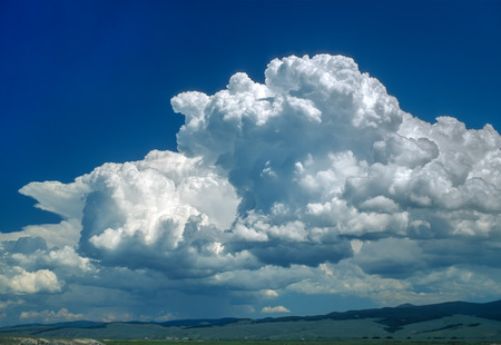cloud formations: Huge puffy cumulus cloud formations surrounded by deep blue vivid sky. Clouds range from pure white to dark gray. Ultra wide angle landscape perspective with just the very bottom of the image showing land horizon in this skyscape. Big Hole Valley, Montana