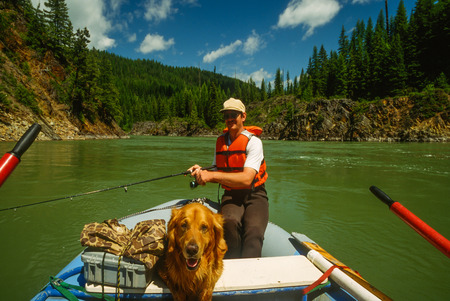 facing right: Ultra wide angle image of a man fishing from a raft with his dog, a big golden retriever. The river originates in high glacial waters so it has very vivid green color. The dog is facing right into the camera and its a beautiful sunny late spring day. Nor