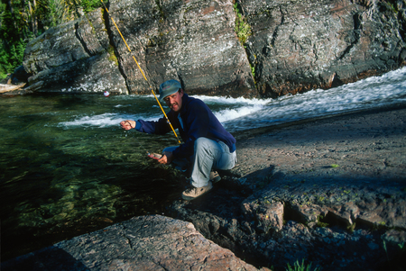 wilderness area: Man holding a trout he just caught from a gorgeous high mountain stream on a clear early morning summer day. Very rocky high mountain wilderness area.
