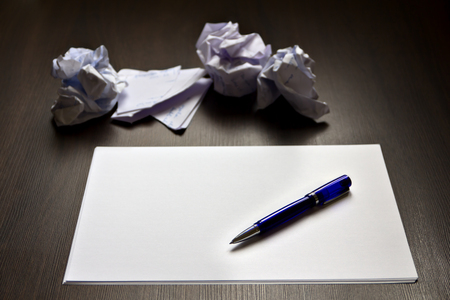 described: Ballpoint pen on a clean paper and crumpled described papers