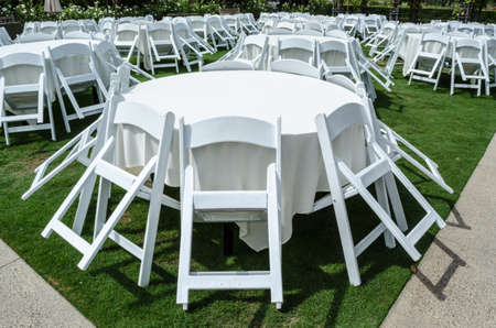 Large round white tables and chairs on lawn.