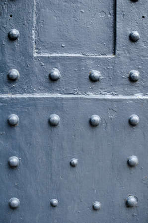 Grey painted steel beam with a uniform pattern of rivets.