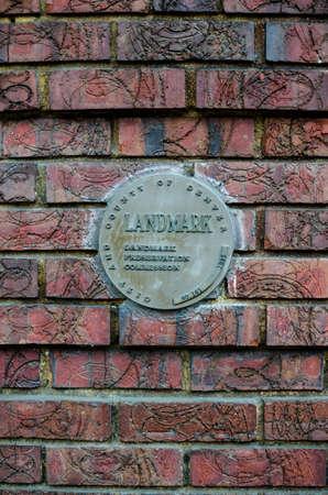 Landmark plaque embeded in brick wall on side of building. Sajtókép