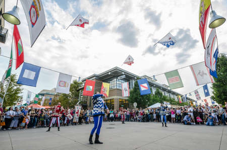 enact: Lakewood, Colorado, September 7, 2014. Festival Italiano at Belmar. An enthusiastic audience watches as Gli Sbandieratori (flag throwers) enact an traditional routine.