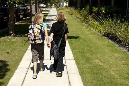 Two elementary age kids with backpacks walking to school.