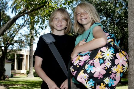 Two Elementary Age Kids with Backpacks in the Schoolyard. photo