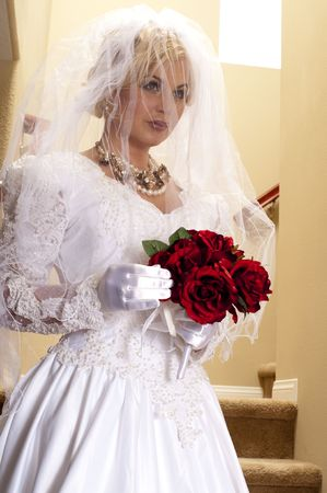 striptease: Bride on Staircase with Lace Veil Covering Her Face Stock Photo
